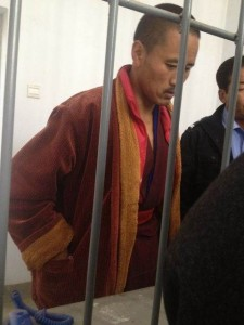 An unshaven and gaunt-looking Gartse Jigme being questioned at Public security Bureau office in Rebkong.