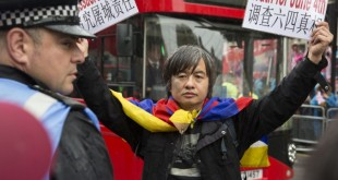 Dr. Shao Jiang wearing a Tibetan flag and holding protest banners during the protest in London (Photo: Epoch Times)