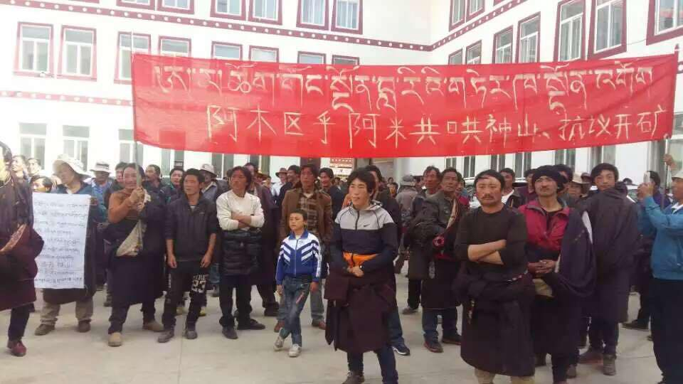 "Anti-mining protesters in Amchok with the banner the in background bearing the slogan: ""Stop Mining at Amchok Gong Ngon Lari!"""